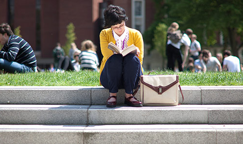 Student reading sat on steps outside on campus